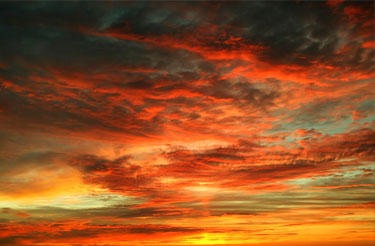 Dramatic sunset skyscape with rich deep red, yellow and orange clouds